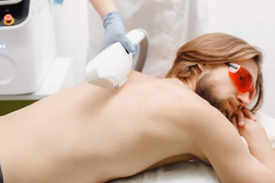 Mann liegt mit Schutzbrille auf einer Liege und lässt eine dauerhafte Laser-Haarentfernung am Rücken durchführen