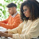 Junge Menschen arbeiten konzentriert an Laptops in Start-up-Atmosphäre