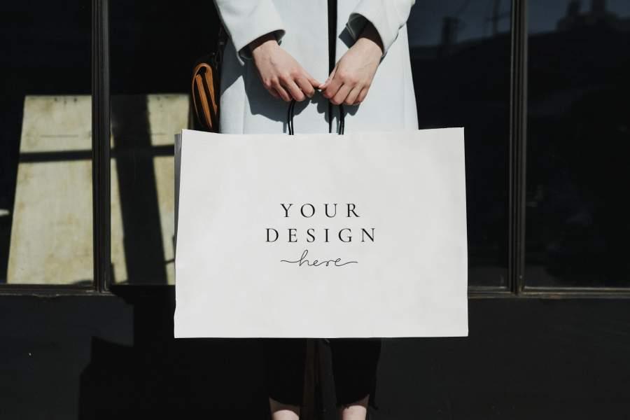 """Papiertasche mit dem Aufdruck """"Your Design here"""" gehalten von den Händen einer Frau in Mantel"""