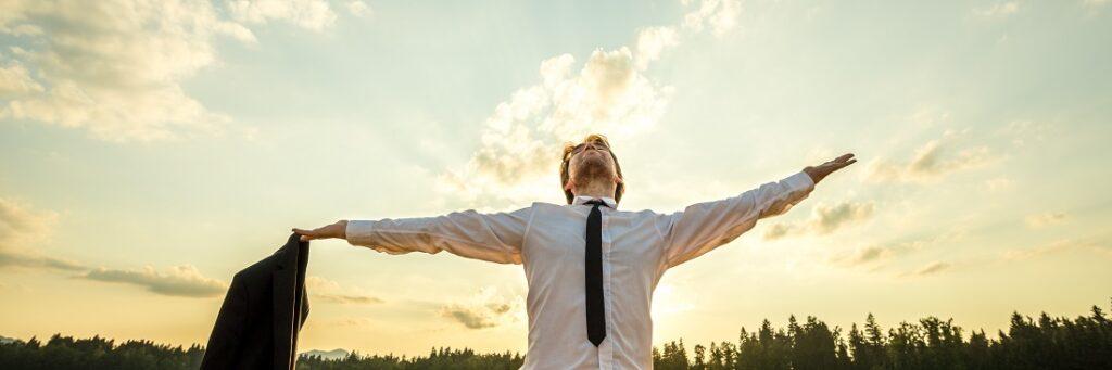 Manager steht in der Abendsonne und streckt die Arme in den Himmel: Trennung von Arbeit und Privatleben