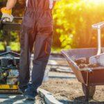 Mann in Arbeitskleidung und Handschuhen zementiert Fundament für Gartenweg