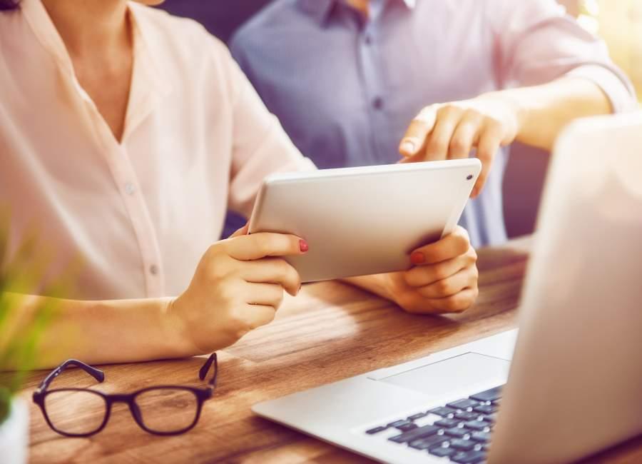 Eine Frau und ein Mann an einem Schreibtisch mit Tablet, Laptop, Brille und Grünpflanze