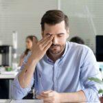 Mann in Hemd sitzt in Großraumbüro am Schreibtisch, nimmt seine Brille ab und reibt sich die Augen