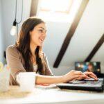 Gut gelaunte junge Frau arbeitet an einem Laptop im Wohnzimmer