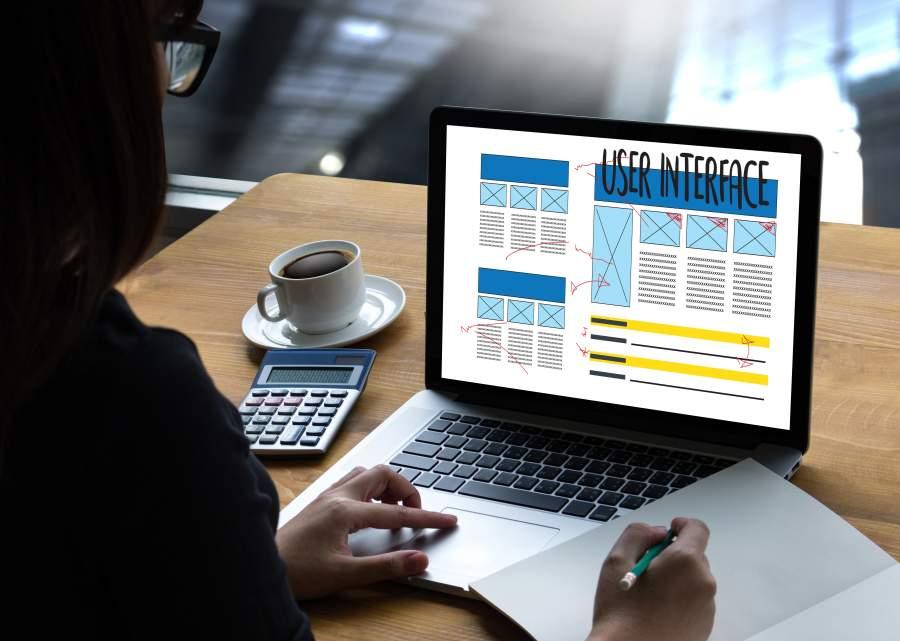 Person arbeitet an einem Laptop, auf dem ein User Interface Mockup für Webdesign abgebildet ist