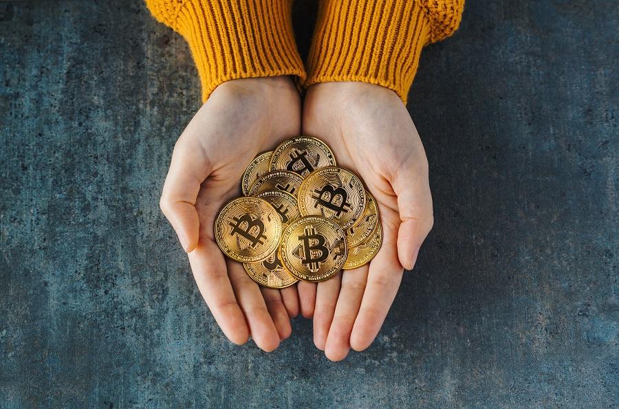Haende mit Bitcoin Münzen von oben gesehen