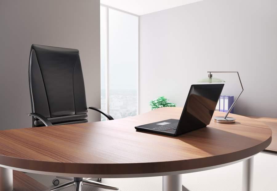 Aufgeräumter Büroraum mit Schreibtisch, Laptop, Tischlampe und Bürostuhl sowie Büromöbeln im Hintergrund