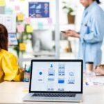 Menschen in einem kreativen Agentur-Arbeitsumfeld in einem Meetingraum, im Vordergrund steht ein Laptop mit Screen-Design