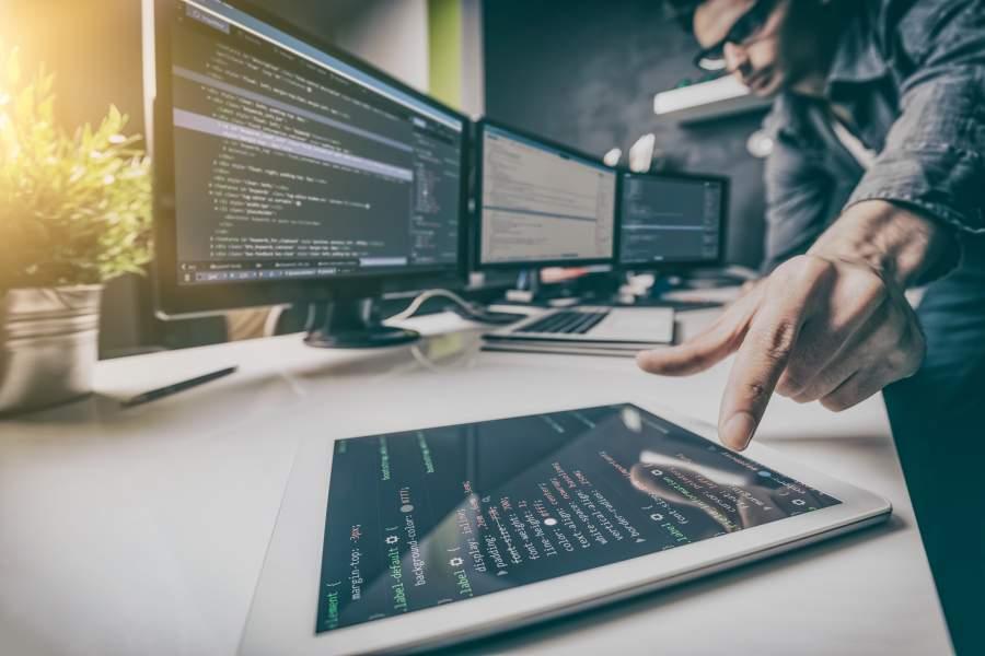 Mann in dunklem Hemd mit Brille zeigt auf Code auf einem Tablet, auf drei weiteren Desktop-Bildschirmen ist weitere individuelle Programmierung zu sehen