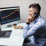 Mann in Hemd und Jeans sitzt an Schreibtisch mit Laptop, Bildschirm, Tastatur und Kaffeebecher, betrachtet Aktienkurse und telefoniert mit Smartphone