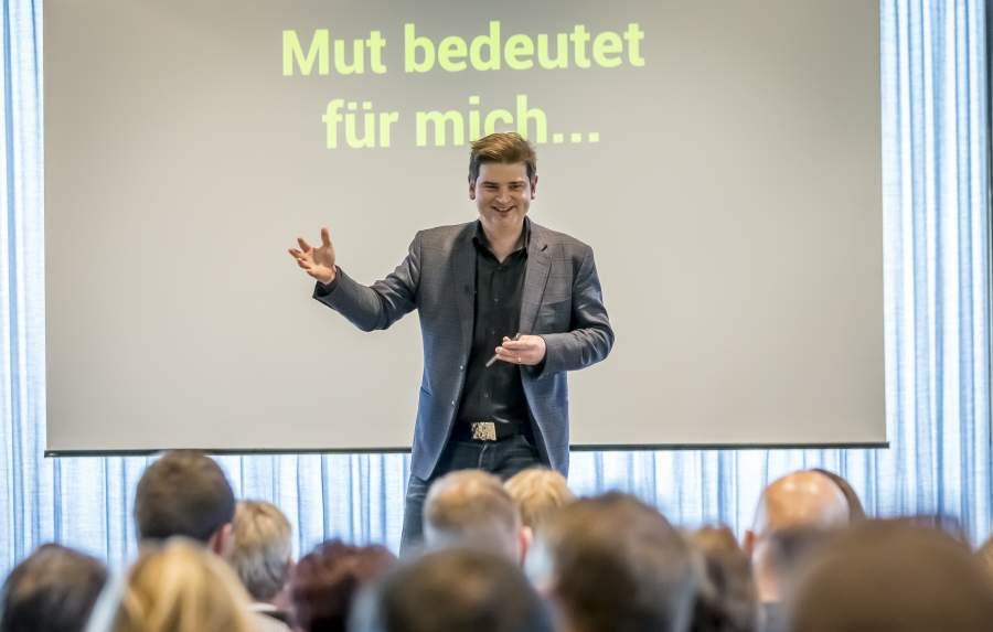 """Autor Lorenz Wenger auf der Bühne, im Hintergrund der Schriftzug """"Mut bedeutet für mich"""""""