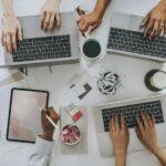 Vogelperspektive auf einen Tisch mit Laptops, Tablets, Smartphones und Arbeitsunterlagen, Menschen arbeiten an den Geräten
