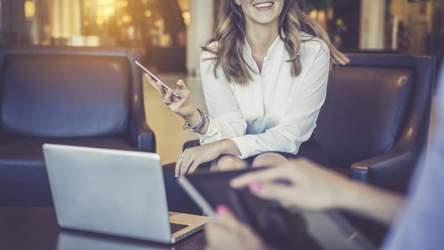 Zwei Business-Frauen sitzen in Leder-Polstermöbeln im Innenbereich und arbeiten mit Tablet, Smartphone und Laptop