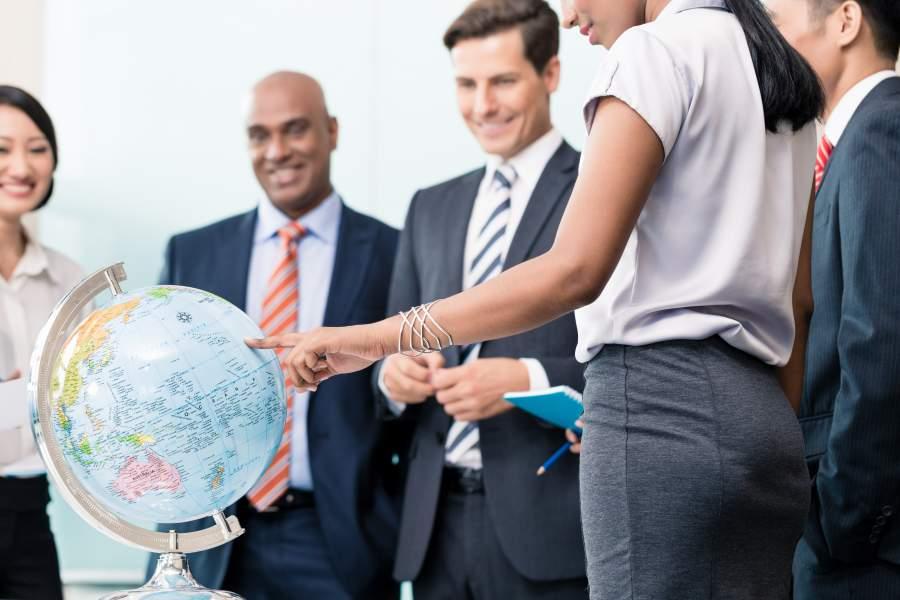 Geschäftsmenschen stehen um einen Globus herum, eine Frau deutet auf einen Punkt auf der Nordhalbkugel