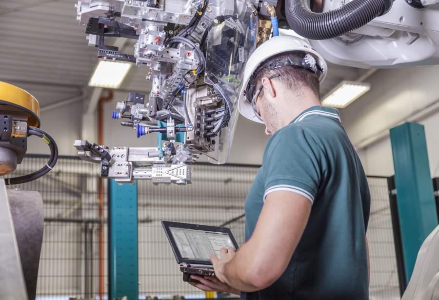 Mitarbeiter in Poloarbeitshemd und Schutzhelm in Robotik-Betriebsstätte bedient Tablet mit Systemdaten