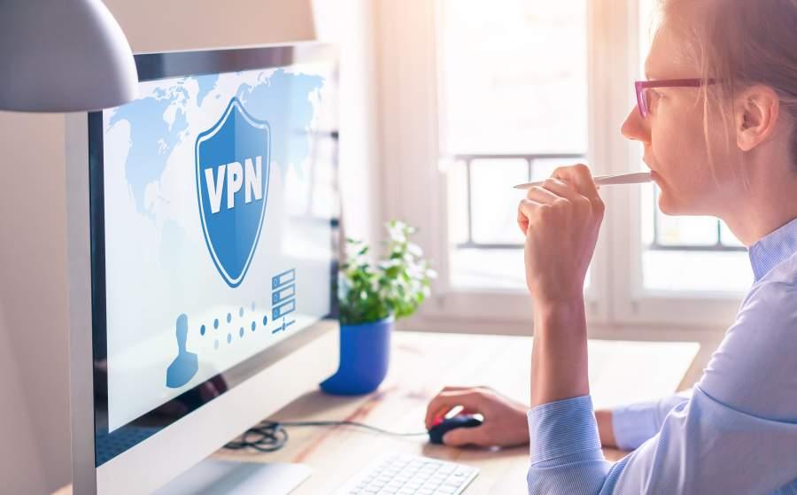 Frau arbeitet an einem Schreibtisch mit Working Station und Monitor, auf dem Bildschirm: Verbindung mit einer VPN-Anwendung für besseren Datenschutz