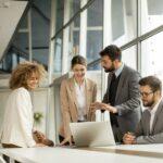 Diverses Team von Geschäftsleuten in einem großen Meetingraum an einem Laptop lächeln im Gespräch